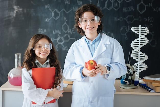 Bereit, die wissenschaftswelt zu erobern. lächelnde, geschickte schüler, die im labor stehen und die wissenschaft erforschen, während sie an dem projekt arbeiten und freude ausdrücken