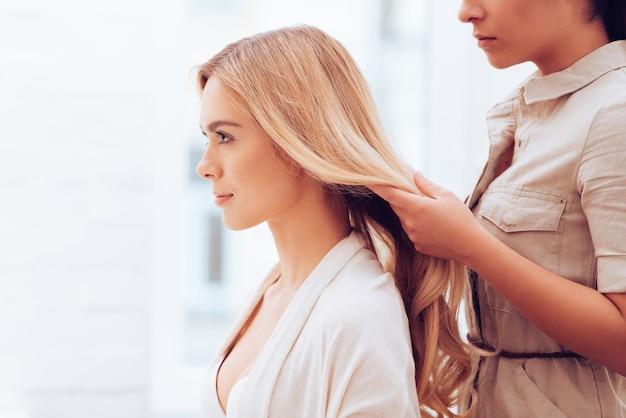 Bereit für das shooting. seitenansicht nahaufnahme einer schönen jungen frau, die wegschaut, während der friseur ihr haar im make-up-raum anpasst