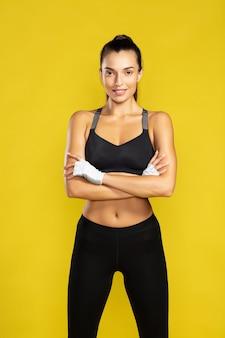 Bereit für das training junge schöne frau in sportkleidung, die die arme verschränkt hält und in die kamera schaut