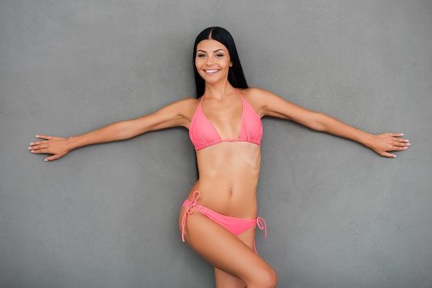 Bereit für den sommer! glückliche junge frau im badeanzug, die die arme ausgestreckt hält und lächelt, während sie vor grauem hintergrund posiert