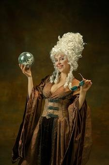 Bereit für die party. porträt der mittelalterlichen jungen frau in der weinlesekleidung mit discoball, brille auf dunklem hintergrund. weibliches modell als herzogin, königliche person. konzept des vergleichs von epochen, mode, schönheit.