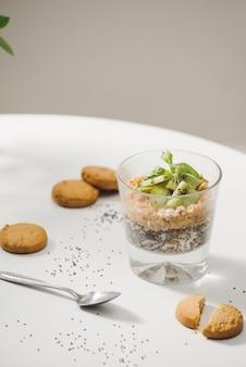 Bereit für ein gesundes und nahrhaftes frühstück - müsli mit mandeln, chiasamen, bananen und kiwis und beeren und ein glas mit milch in der nähe