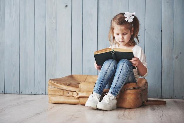 Bereit für große reisen. glückliches kleines mädchen, das das intereting buch trägt einen großen aktenkoffer und ein lächeln liest. reisen, freiheit und vorstellungskraft