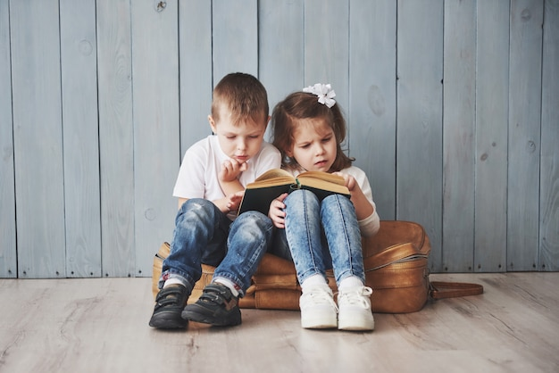 Bereit für große reisen. glückliches kleines mädchen und junge, die das intereting buch trägt einen großen aktenkoffer und ein lächeln liest. reisen, freiheit und vorstellungskraft