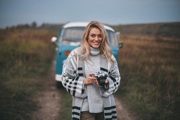 Bereit für gute aufnahmen. attraktive junge frau, die digitalkamera hält und lächelt, während sie draußen mit dem blauen retro-art-minivan steht