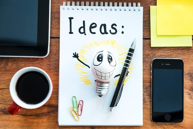 Bereit für tolle ideen. draufsicht auf notizblock mit kaffeetasse auf dem holzschreibtisch mit verschiedenen geschäftssachen drumherum