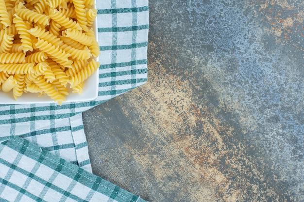 Bereit, fusilli-nudeln in einer schüssel auf einem handtuch auf der marmoroberfläche zu kochen.