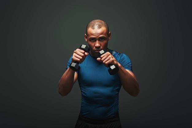 Bereit, gut aussehender junger sportler zu kämpfen, der mit hanteln auf dunklem hintergrund trainiert