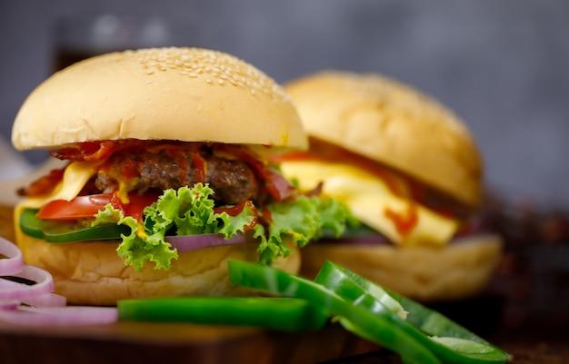 Bereit, hausgemachten hamburger und frische zutaten mit einem glas getränk im hintergrund zu essen. aufgenommen mit dunklem licht.