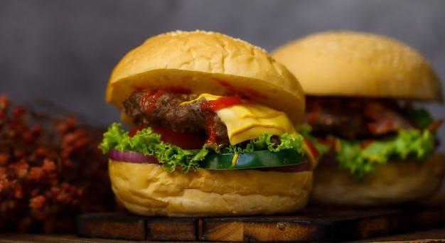 Bereit, hausgemachten schweinefleisch-hamburger mit kopienraum im dunklen hintergrund zu essen.