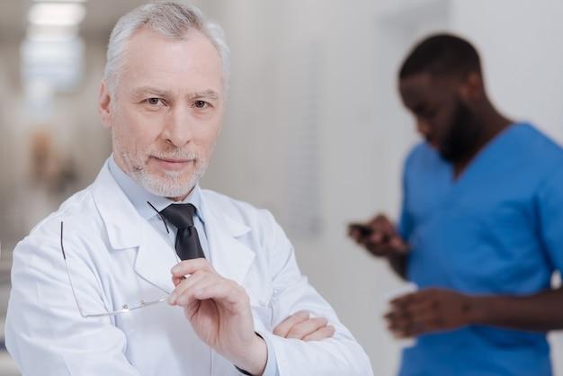 Bereit, nützliche ratschläge zu geben. zuversichtlich kompetenter leitender arzt, der in der klinik steht und brille hält, während afroamerikanischer kollege gerät im hintergrund verwendet