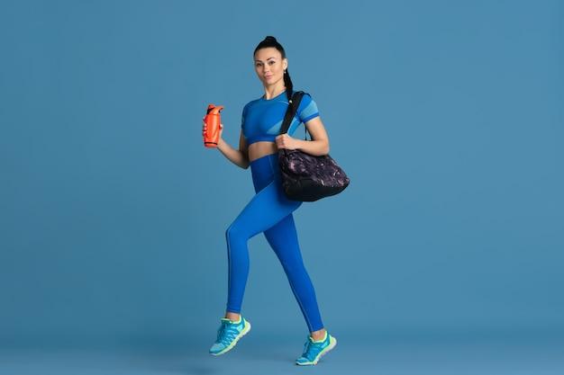 Bereit. schöne junge sportlerin üben, einfarbiges blaues porträt. sportlich sitzendes brünettes modell mit wasserflasche und tasche. wellness, gesunder lebensstil, schönheits- und aktionskonzept.