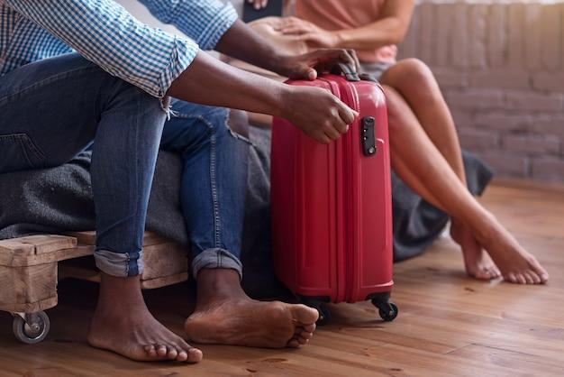 Bereit sein. schließen sie oben von der internationalen jungen glücklichen paarverpackung für eine reise und bereiten sie sich auf flitterwochen vor, während sie zeit zusammen verbringen.