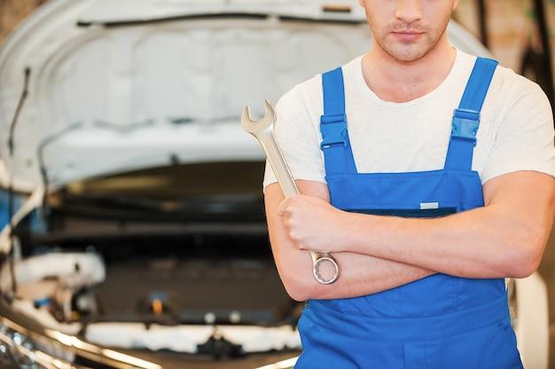 Bereit zu arbeiten. nahaufnahme eines selbstbewussten jungen mannes, der einen schraubenschlüssel hält, während er in der werkstatt mit dem auto im hintergrund steht