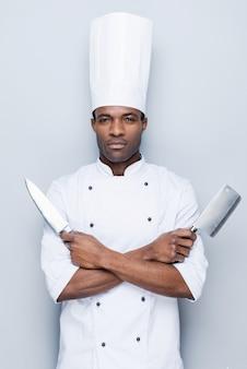 Bereit zu arbeiten. selbstbewusster junger afrikanischer koch in weißer uniform, der messer in den händen hält
