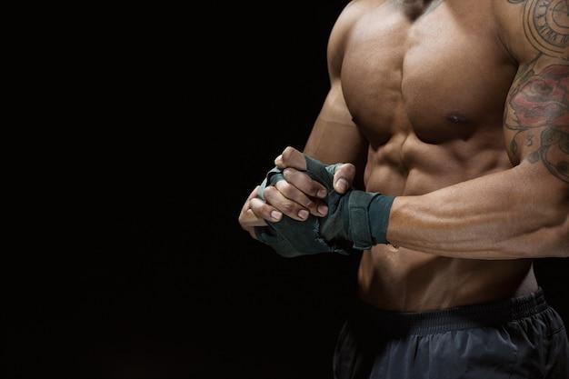 Bereit zu überwinden. kurzer schuss eines torsos eines professionellen kämpfers mit seinen bandagen beim vorführen seines perfekten abdomens