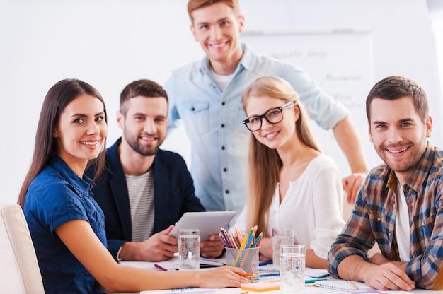 Bereit zum brainstorming. gruppe glücklicher geschäftsleute in eleganter freizeitkleidung, die zusammen am tisch sitzen und in die kamera schauen