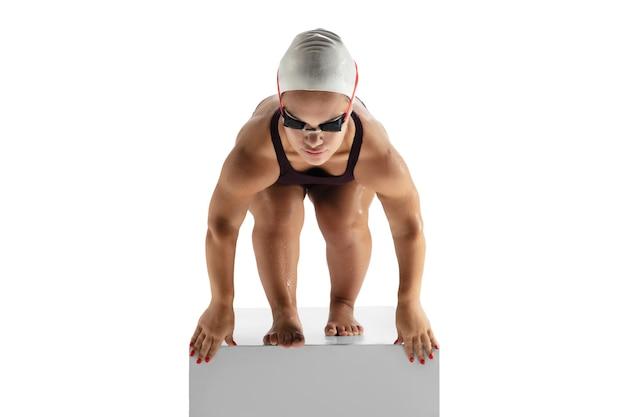 Bereit zum handeln. schöne kleine frau, die beim schwimmen lokalisiert auf weißem hintergrund übt. lebensstil inklusiver menschen, vielfalt und gleichberechtigung. sport, aktivität und bewegung. exemplar für anzeige.
