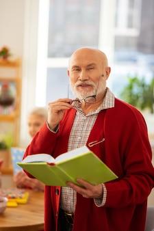 Bereit zum lesen. glücklicher gutaussehender mann, der seine brille trägt, während er mit einem buch steht