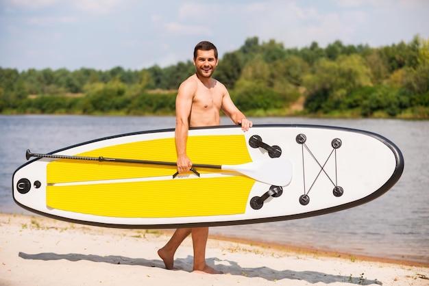 Bereit zum paddeln. hübscher junger mann, der sein paddleboard beim gehen am flussufer hält