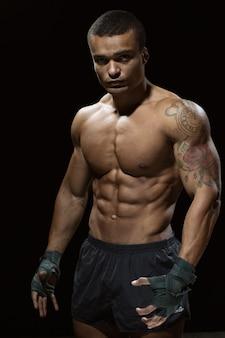 Bereit zum start. vertikales porträt eines schönen boxers mit atemberaubendem zerrissenem körper