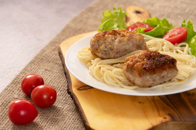 Bereite fleischpastetchen mit salat in einer platte auf dem tisch.