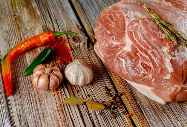 Bereiten sie die schweineschulter zum kochen mit gewürzen auf holzoberfläche vor