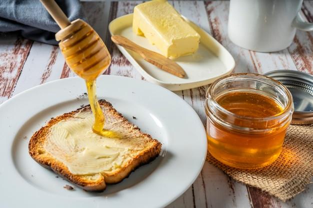 Bereiten sie ein gesundes frühstück mit einem toast mit butter und reinem bio-bienenhonig zu. gesundes lebensmittelkonzept. Premium Fotos