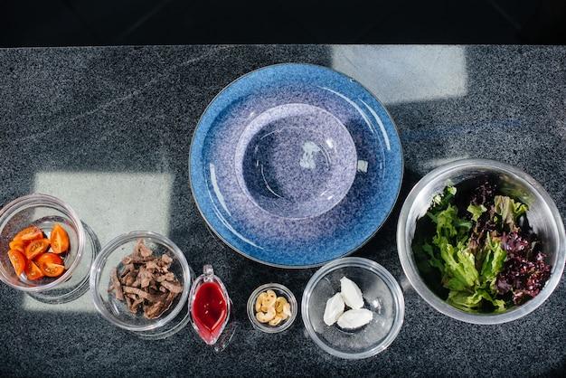 Bereiten sie einen köstlichen frischen salat aus tomatengrün, käse, kalbfleisch und cashewnüssen zu. leckeres gesundes essen.