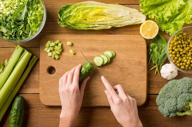 Bereiten sie einen salat aus frischem gemüse zu. frische gurke auf einem schneidebrett schneiden. weibliche hände.