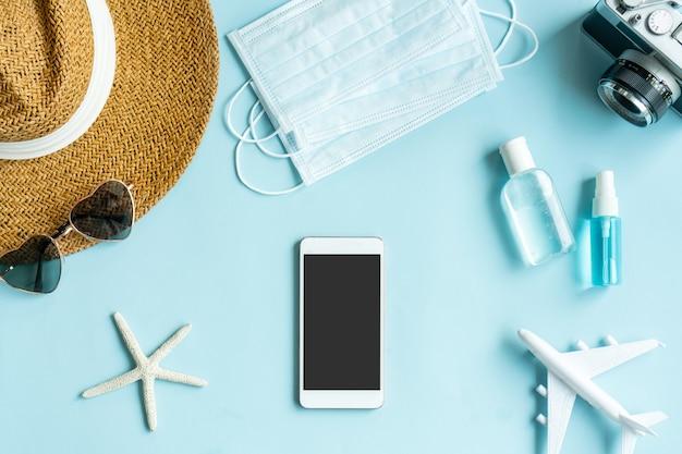 Bereiten sie reiseartikel auf blauem schreibtisch vor. planung einer reise während der coronavirus-pandemiekonzepte. platz kopieren.