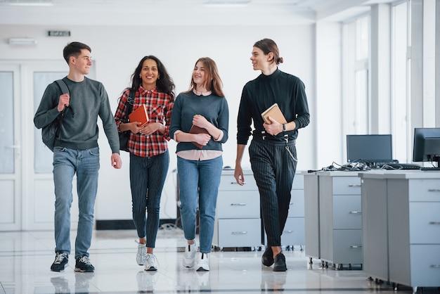 Bereiten sie sich auf die heutige arbeit vor. gruppe junger leute, die in ihrer pause im büro spazieren gehen.