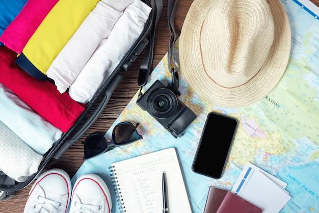 Bereiten sie zubehör und reiseartikel für eine neue reise vor und packen sie ihre kleidung in der koffertasche auf holzbrett