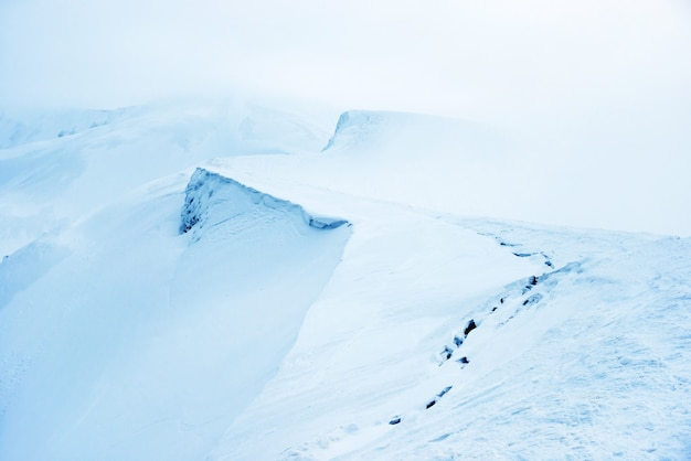 Berg im blauen schnee mit nebel. winterlandschaft