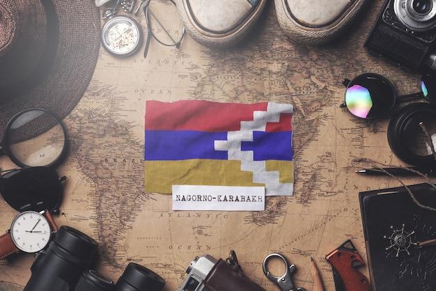 Berg-karabach-flagge zwischen dem zubehör des reisenden auf alter weinlese-karte. obenliegender schuss