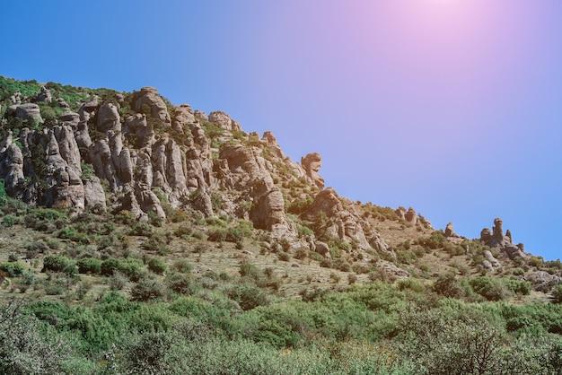Berg mit grünen bäumen vor einem klaren himmel mit buntem hintergrund der sonnenstrahlen