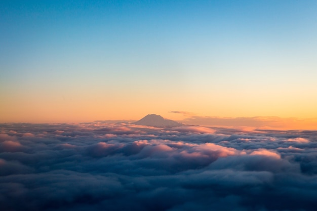 Berg über weißen wolken während des tages