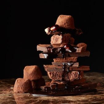 Berg von stücken dunkler schokolade mit schokoladentropfen auf einer marmoroberfläche