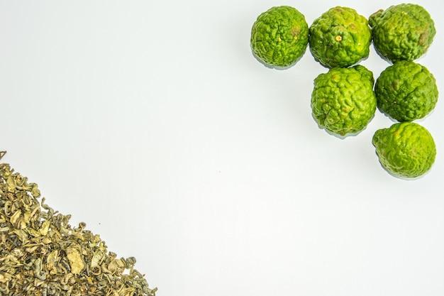 Bergamotte früchte und tee. citrus bergamia, die bergamotte-orange ist eine duftende zitrusfrucht mit einer gelben oder grünen farbe ähnlich einer limette.