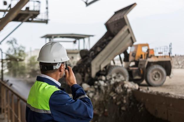 Bergbauingenieur in gelb-blauer uniform und helm überwacht das entladen von muldenkippern
