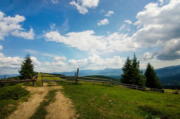 Bergblick mit grünem himmel des weißen himmels der grünen wolken des hölzernen zauns