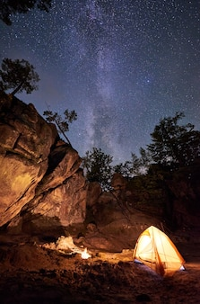 Bergcampingplatz in der sommernacht inmitten einer riesigen steilen felsformation. kleines touristenzelt hell beleuchtet durch brennendes lagerfeuer unter klarem dunklem sternenhimmel mit milchstraße. tourismus-, wander- und reisekonzept