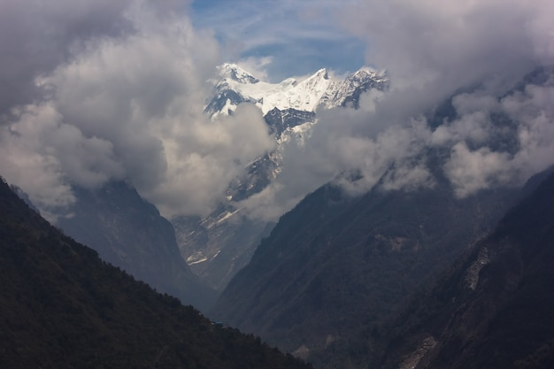 Berge bedeckt mit schnee und einem nebligen himmel
