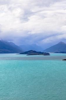 Berge, die von den seeinseln auf wakatipu-see neuseeland wachsen