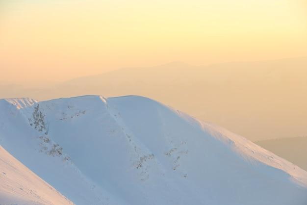 Berge im schnee. landschaft mit sonnenuntergang über hügeln
