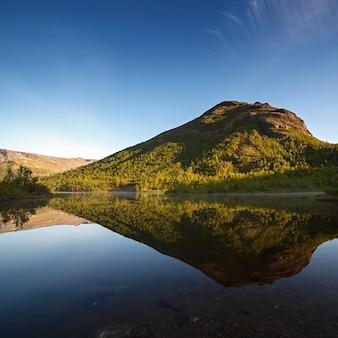 Berge spiegelten sich im morgengrauen in der glatten oberfläche des sees.