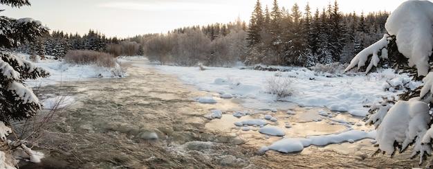 Bergfluss friert an einem kalten wintermorgen mit nebel aus dem wasser ein