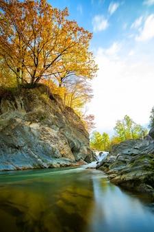 Bergfluss mit kleinem wasserfall mit klarem türkisfarbenem wasser, das an einem hellen herbsttag zwischen nassen felsbrocken mit dickem weißem schaum fällt.