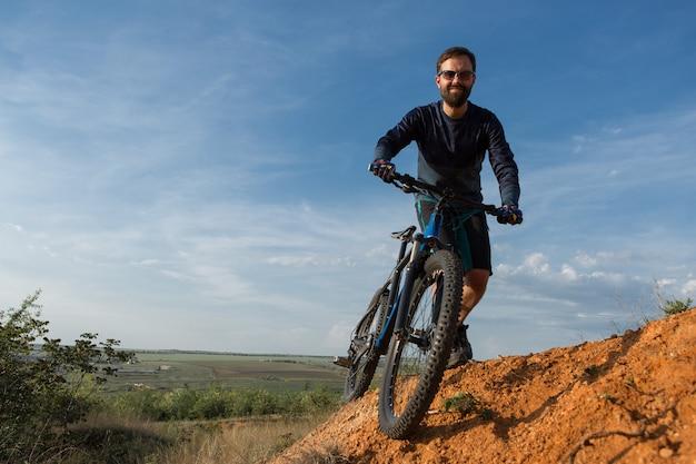Berggipfel erobern mit radler in shorts und jersey auf einem modernen carbon-hardtail-bike