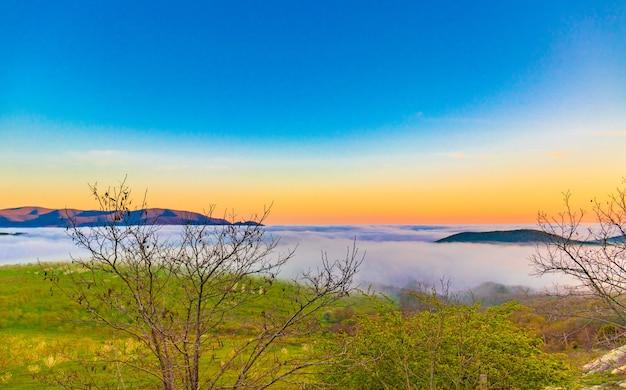 Bergkette mit sichtbaren silhouetten durch den bunten morgennebel. Premium Fotos